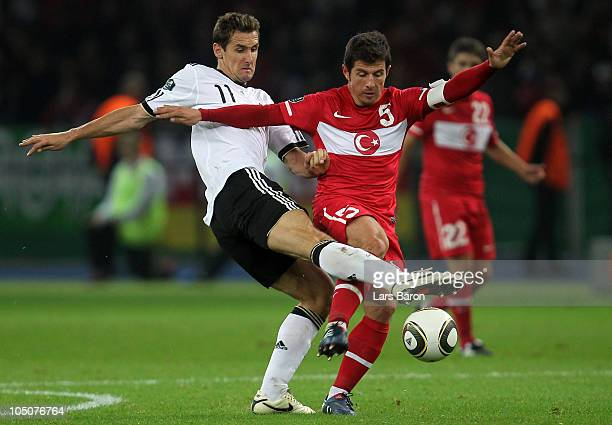 Miroslav Klose of Germany challenges Emre of Turkey during the EURO 2012 Group A qualifier match between Germany and Turkey at Olympic Stadium on...
