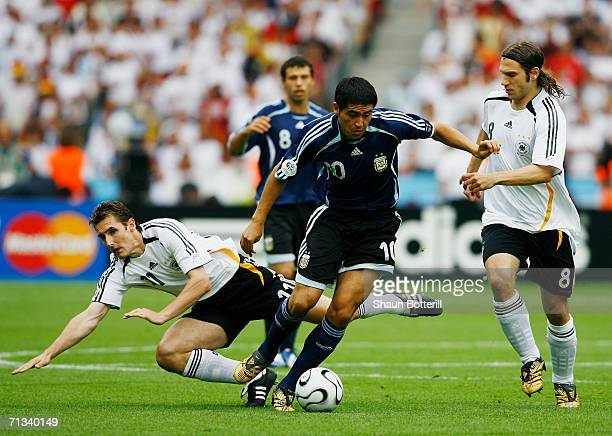 Miroslav Klose of Germany falls to the ground as Juan Riquelme of Argentina surges forward under pressure from Torsten Frings of Germany during the...