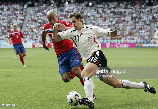 Miroslav Klose of Germany is challenged by Douglas Sequeira of Costa Rica during the FIFA World Cup Germany 2006 Group A match between Germany and...