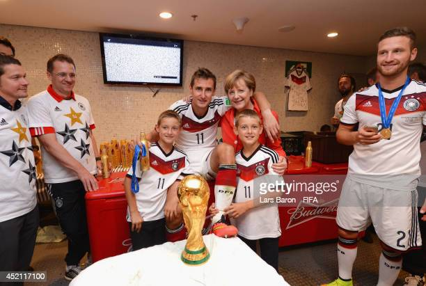Miroslav Klose of Germany poses with German Chancellor Angela Merkel and his sons Luan and Noah in the Germany dressing room after the 2014 FIFA...