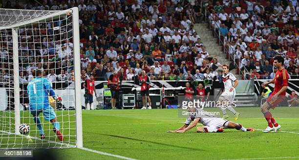 Miroslav Klose of Germany scores his team's fourth goal against goalkeeper Roman Berezovsky of Armenia during the International Friendly match...