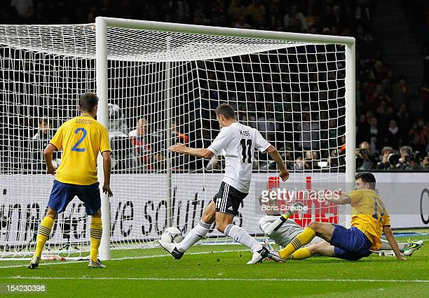 Miroslav Klose of Germany scores their second goal despite the attentions of Mikael Lustig goalkeeper Andreas Isaksson and Behrang Safari of Sweden...
