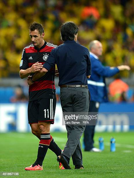 Miroslav Klose of Germany shakes hands with head coach Joachim Loew after being replaced during the 2014 FIFA World Cup Brazil Semi Final match...