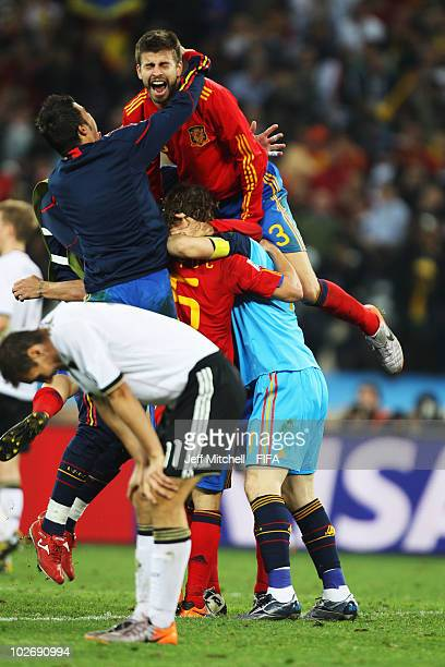 Miroslav Klose of Germany shows his dejection as Gerard Pique of Spain celebrates with teammates Carles Puyol and Iker Casillas during the 2010 FIFA...