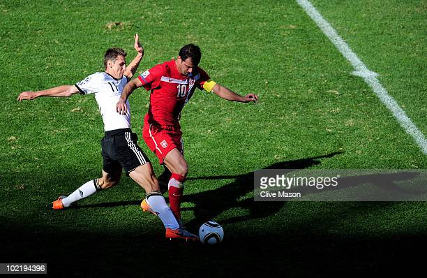Miroslav Klose of Germany tackles Dejan Stankovic of Serbia and then receives a second yellow card and is sent off during the 2010 FIFA World Cup...