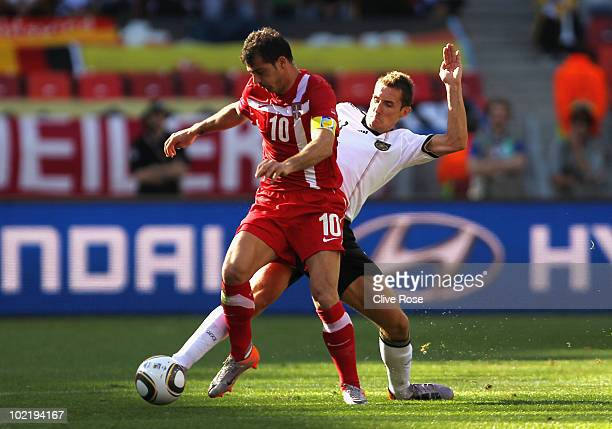 Miroslav Klose of Germany tackles Dejan Stankovic of Serbia during the 2010 FIFA World Cup South Africa Group D match between Germany and Serbia at...