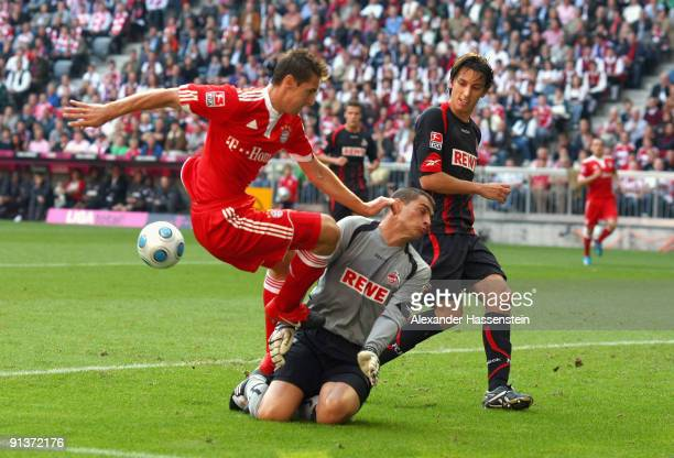 Miroslav Klose of Muenchen battles for the ball with goalkeeper Faryd Mondragon of Koeln and his team mate Pedro Geromel during the Bundesliga match...