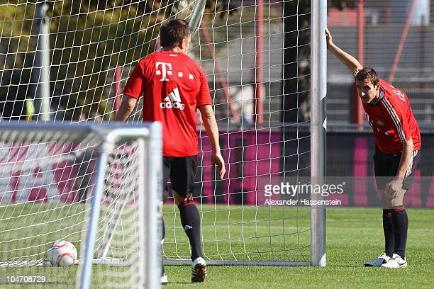Miroslav Klose talks to his team mate Ivica Olic during the Bayern Muenchen training session at Bayern's training ground 'Saebener Strasse' on...