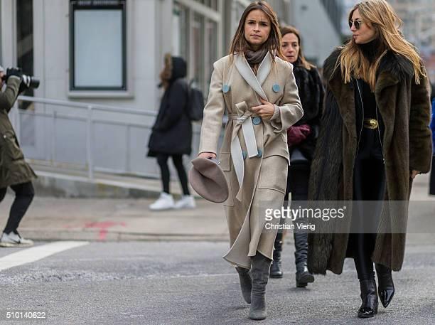 Miroslava Duma wearing a creme wool coat and a beret and Nasiba Adilova wearing a green fur coat and Ray Ban sunglasses seen outside Jason Wu during...