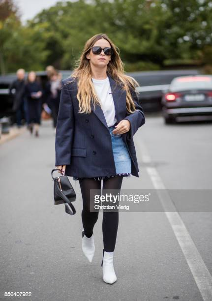 Miroslava Duma wearing navy blazer denim mini skirt tights white boots seen outside Balenciaga during Paris Fashion Week Spring/Summer 2018 on...