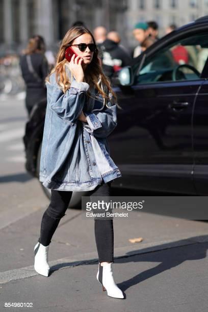 Miroslava Duma wears a blue denim jacket outside the Dries Van Noten show during Paris Fashion Week Womenswear Spring/Summer 2018 on September 27...