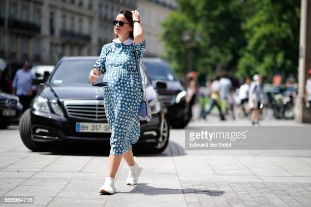 Miroslava Duma wears a blue dress with white dots and a Vuitton bag outside the Louis Vuitton show during Paris Fashion Week Menswear Spring/Summer...