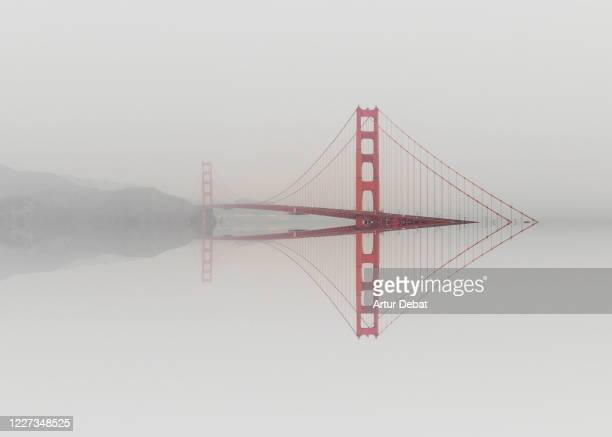 mirror distortion effect of the golden gate bridge emerging from water. - san francisco california stock pictures, royalty-free photos & images