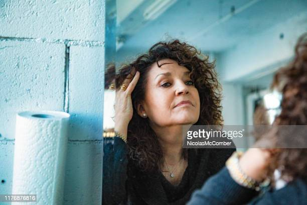 mirror image of a pensive senior woman looking at her aging face - grey hair stock pictures, royalty-free photos & images