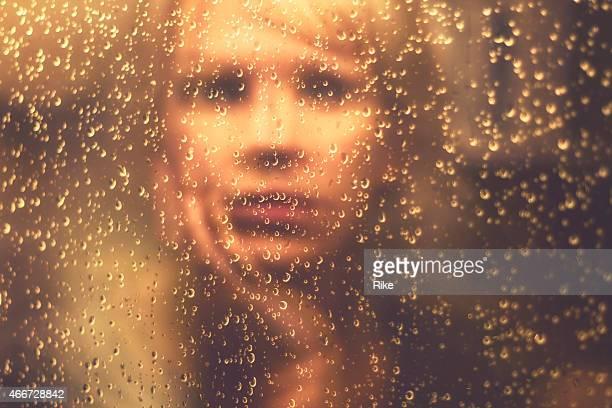 Espejo imagen de una mujer con gotas de lluvia en la ventana