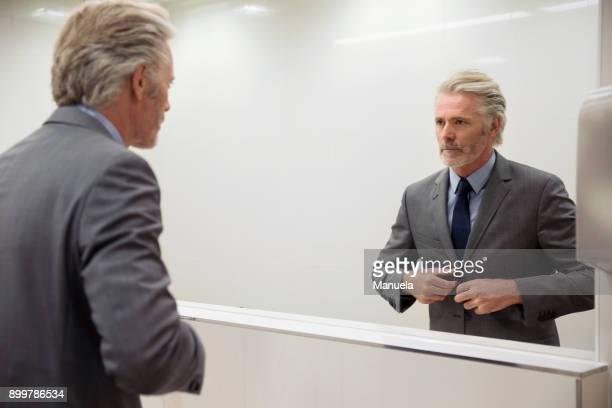 Mirror image of man looking into mirror