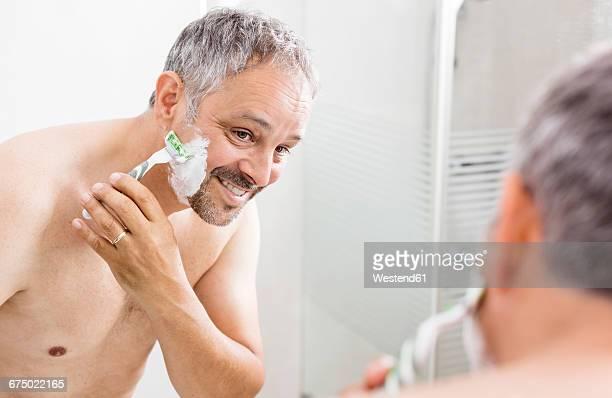Mirror image of shaving man