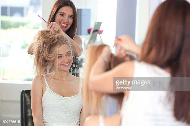 Mirror image of teenage girl and hairdresser at hair salon