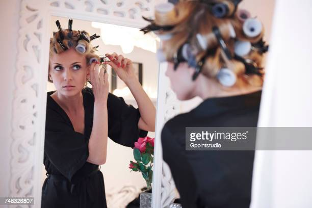 Mirror image of woman putting in hair rollers