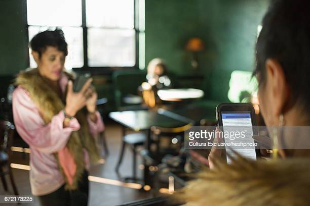 mirror image of woman reading smartphone in recreational bar - heshphoto stock pictures, royalty-free photos & images