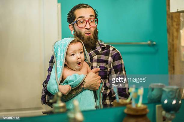Mirror image of young man and baby son pulling faces in bathroom