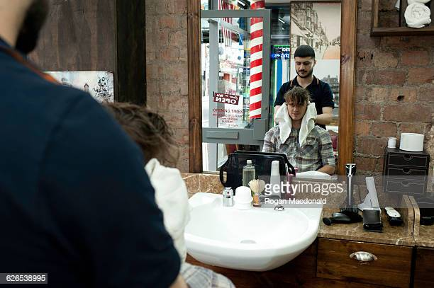 Mirror image of young man and barber in barbershop