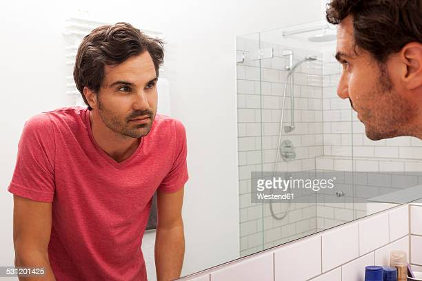 Mirror image of young man watching himself