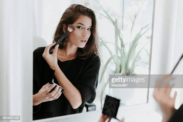 mirror image of young woman applying makeup - make up stock pictures, royalty-free photos & images