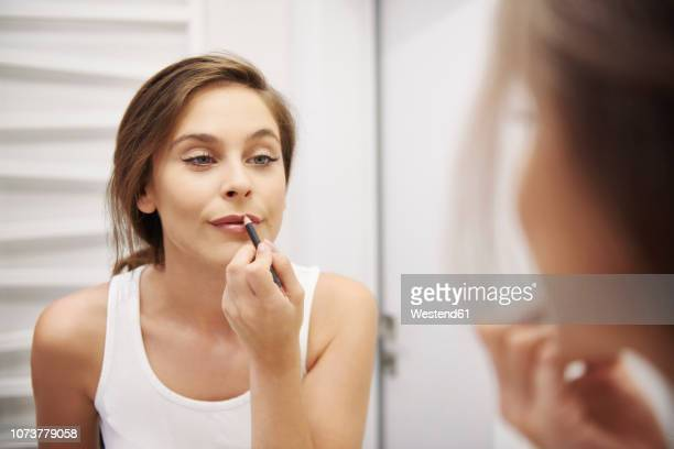 mirror image of young woman in bathroom applying lipliner - lip liner stock photos and pictures