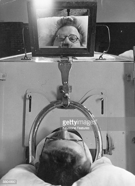 A mirror placed on top of his Iron Lung enables Mr Evans a paralysis sufferer to see who is entering his room
