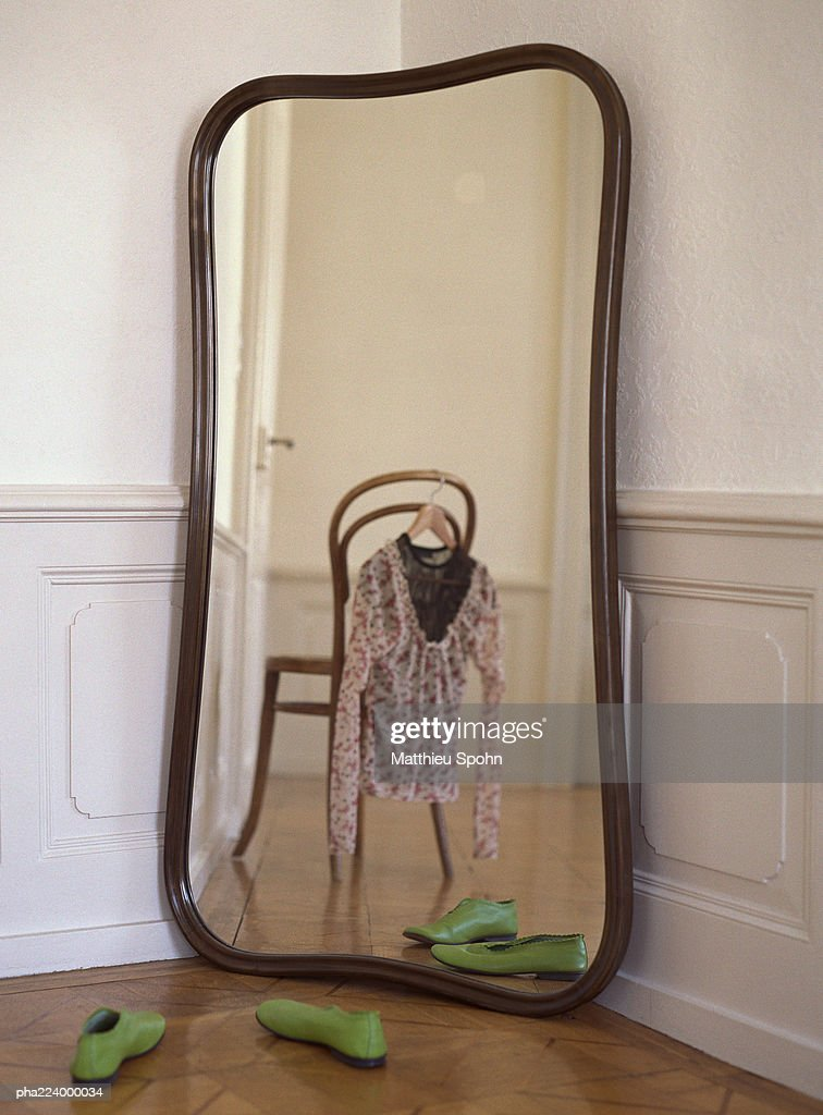 Mirror reflecting chair with blouse hanging from it. : Stockfoto