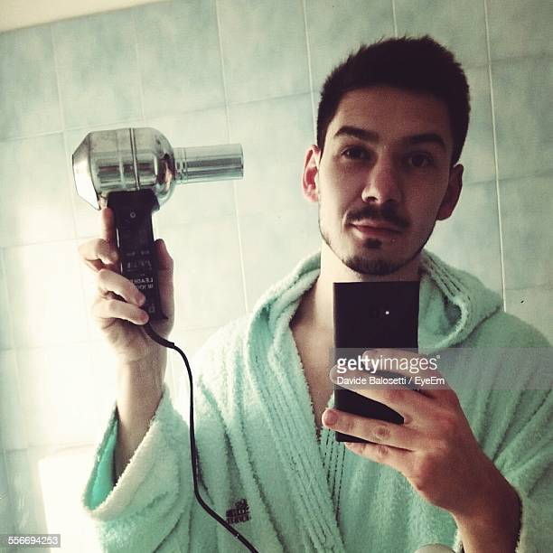 Mirror Reflection Of Man Taking Selfie From Cell Phone In Bathroom