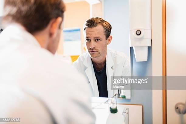 mirror reflection of mid adult male doctor in hospital bathroom - casaco - fotografias e filmes do acervo