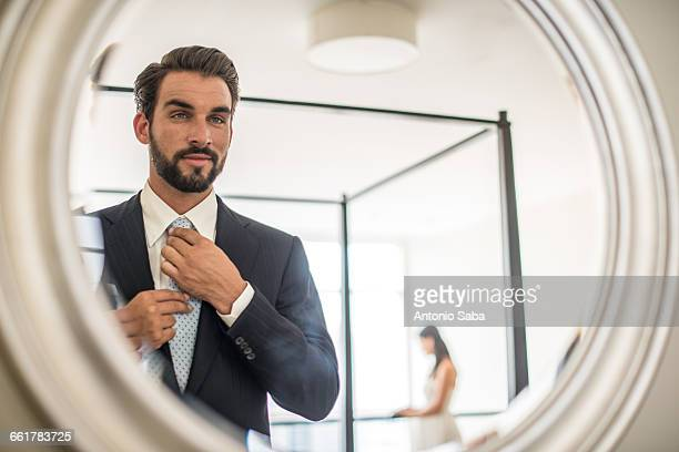 mirror reflection of young businessman adjusting shirt and tie in hotel room, dubai, united arab emirates - capital stock pictures, royalty-free photos & images