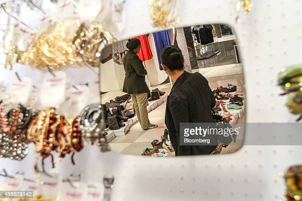 Mirror reflects customers browsing women's footwear for sale inside a Truworths International Ltd. Fashion store in Sandton, South Africa, on...