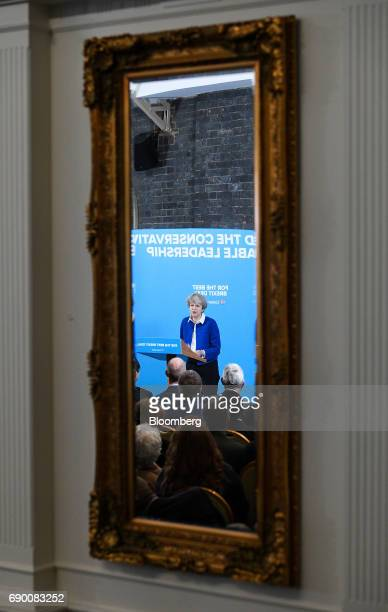 A mirror reflects Theresa May UK prime minister and leader of the Conservative Party as she speaks during a generalelection campaign event in...