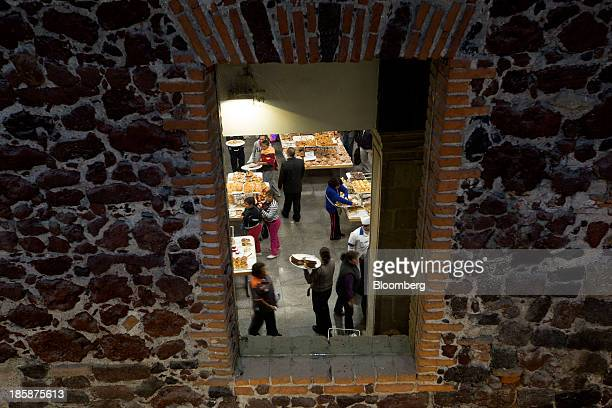 A mirror shows the reflection of customers at La Ideal bakery in Mexico City Mexico on Thursday Oct 24 2013 The pan de muerto or bread of the dead is...