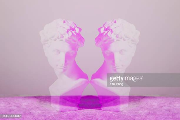 mirrored image of sculpture facing each other - vanity stock pictures, royalty-free photos & images