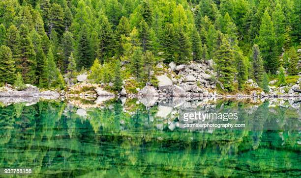 """Mirror-like green mountain lake """"Saoseo"""" with reflections of trees and rocks"""