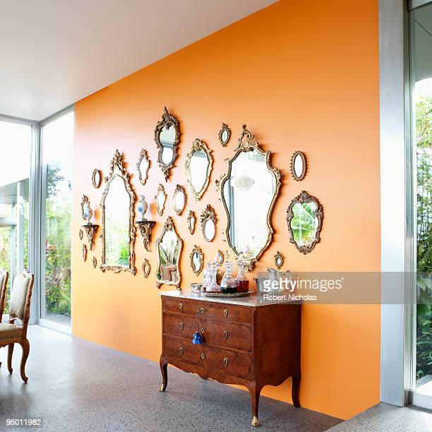mirrors on orange wall - quadratisch komposition stock-fotos und bilder