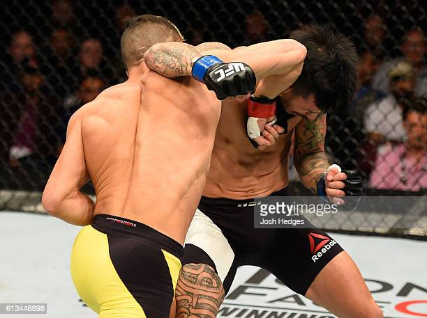 Mirsad Bektic of Bosnia punches Russell Doane in their featherweight bout during the UFC 204 Fight Night at the Manchester Evening News Arena on...