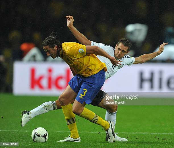 Mirsolav Klose of Germany challenges for the ball with Jonas Olsson of Sweden during the FIFA 2014 World Cup qualifier group C match between German...
