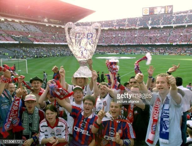 Mirt der Nachbildung eines Pokals feiern am Fans des deutschen Rekordmeisters FC Bayern München ihren Verein kurz vor dem Anpfiff zum...
