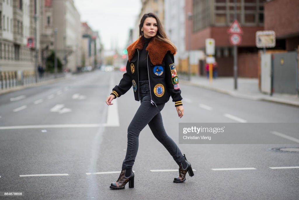 Miryam Labiad wearing Coach jacket, grey skinny jeans Current Elliot, Louis Vuitton boots on October 21, 2017 in Berlin, Germany.
