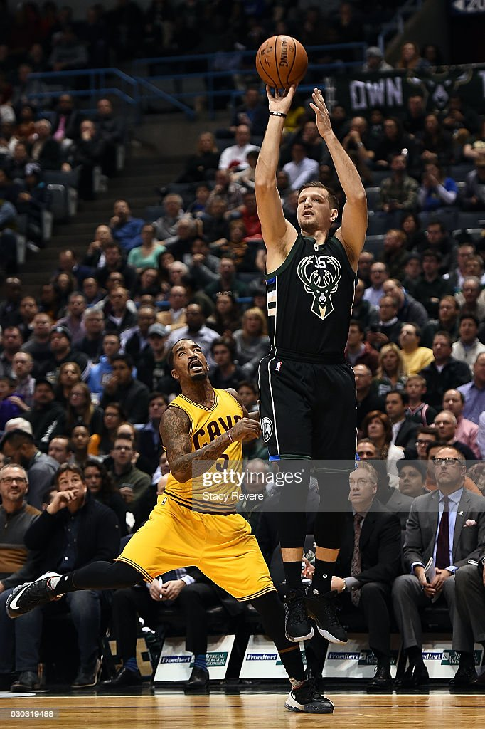 6b2621bdce0c Mirza Teletovic of the Milwaukee Bucks shoots over J.R. Smith of the ...