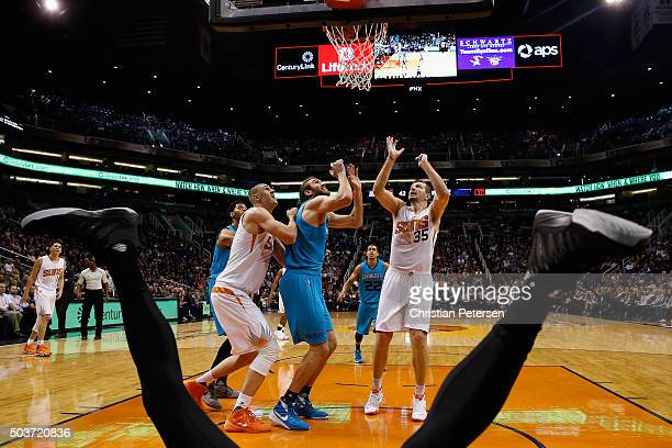 Mirza Teletovic of the Phoenix Suns and Spencer Hawes of the Charlotte Hornets look for a rebound after Jeremy Lamb fell to the court during the...
