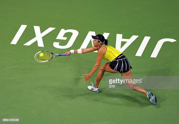 Misa Eguchi of Japan hits a return against Duan Yingying of China during their singles semifinal match at the Jiangxi Open WTA tennis tournament in...