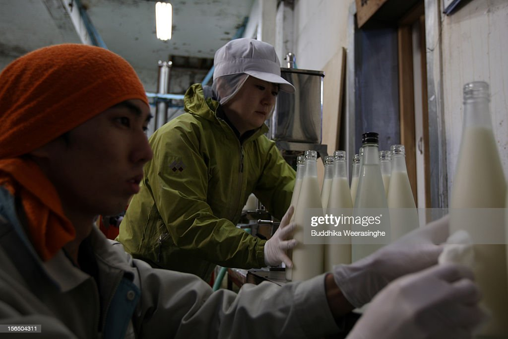 Misa Kawaisi (R), chief sake brew master, fills sake bottle at Nadagiku-Shozo sake brewery on November 16, 2012 in Himeji, Japan. Kawaishi, one of a few female sake brew masters, is a unique figure in male-diminated sake brewers world.