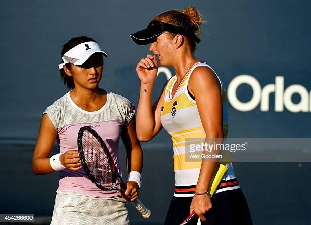 Misaki Doi of Japan talks with Elina Svitolina of Ukraine during their women's doubles match on Day Three of the 2014 US Open at the USTA Billie Jean...