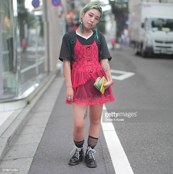 Misaki Yamamoto is wearing a red vintage dress over a black tshirt black Dr Marten boots with white laces fishnet socks vintage jewellery and a...